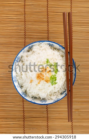 Top view of a bowl of rice with chopsticks - stock photo