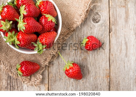 Top view of a bowl with strawberry on wooden background - stock photo