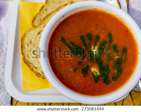top view of a bowl with tomato soup with basil oil and Mozzarella, with on the side corn bread - stock photo