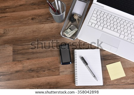 Top view of a business desk with laptop computer, cell phone, money clip, note pad, paper, pen, pen holder car keys with copy space. - stock photo
