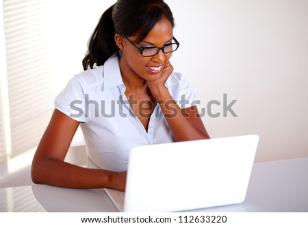 Top view of a charming young black woman with glasses working on laptop at workplace - copyspace - stock photo