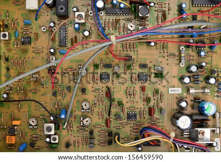 Top view of a circuit board with electrical components and colored cords - stock photo