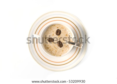Top view of a coffee cup filled with capuccino and coffee beans - stock photo