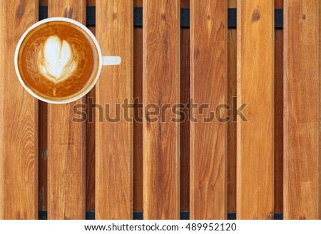 Top view of a coffee with heart pattern in a white cup on wooden plank background, latte art