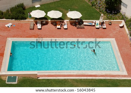 Top view of a condo swimming pool with two empty white deckchairs.