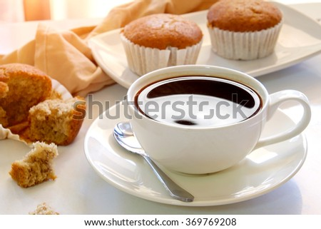 Top view of a cup of coffee and Banana Muffin in a brown baking paper cup. - stock photo