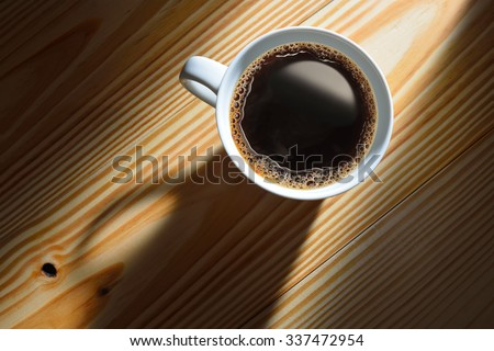 Top view of a cup of coffee in the morning light on wooden background - stock photo