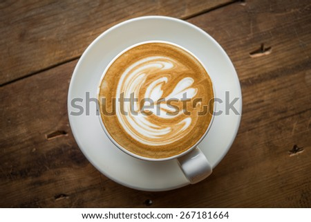 Top view of a cup of coffee latte art on wooden table. - stock photo
