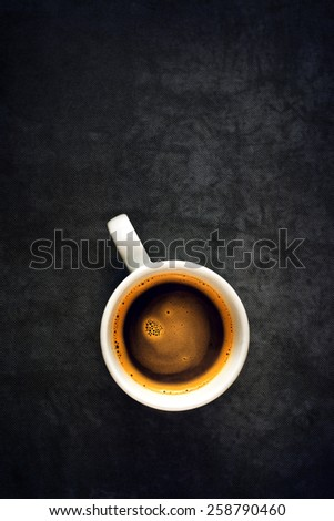 Top View of a Cup of Hot Black Coffee, White Ceramics Mug on Grunge Gray Table Cloth as Copy Space. - stock photo