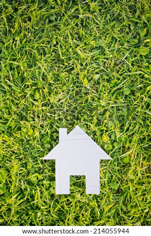 Top view of a cutout paper house over green grass with copy space above it. - stock photo
