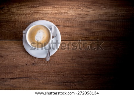 Top view of a delicious Cup of freshly brewed aromatic cappuccino standing on a wooden table. - stock photo