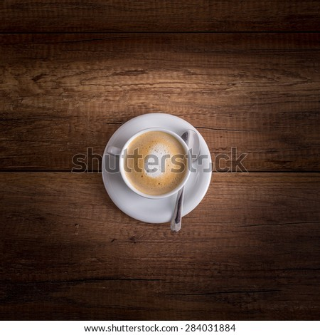Top view of a delicious Cup of freshly brewed hot aromatic cappuccino standing on a wooden table. Square format. - stock photo