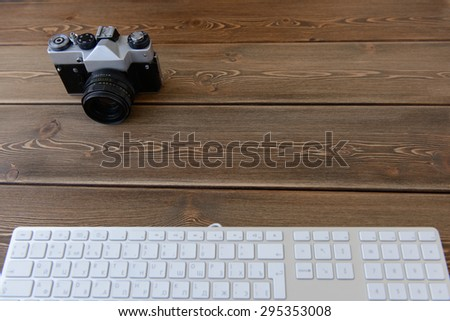 top view of a desktop of a photographer consisting on a camera and keyboard on a dark desk background - suitable for copy space - stock photo