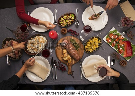 Top view of a dinner table. Roast beef, cauliflower salad, Brussels sprouts, smoked salmon, garlic bread, candle, rice, turkey & red wine. Hands holding cutlery and wine. - stock photo