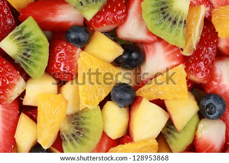 Top view of a fruit salad with strawberries, oranges, kiwi, blueberries and peaches - stock photo