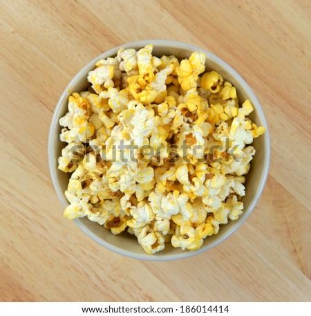 Top view of a full bowl of buttered popcorn on a wood table top. - stock photo