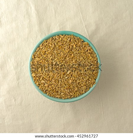 Top view of a full bowl of cracked freekeh grain on a beige tablecloth illuminated with natural light.