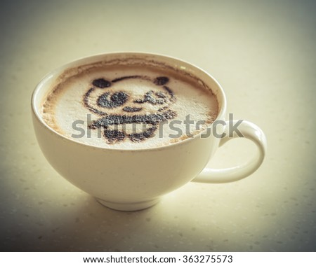 Top view of a giant panda (or panda bear) shape foam art of a cappuccino cup with saucer on wooden table background in the natural light of afternoon. Panda latte art drawing cafe cup in vintage style