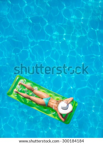 Top view of a  girl in the swimming pool on a lilo - stock photo