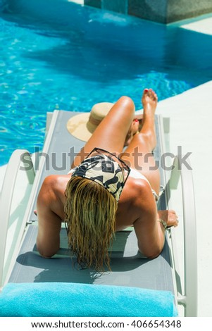 Top view of a girl in the swimming pool on a sunbed
