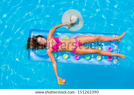 Top view of a  girl with cocktail on a lilo in the swimming pool - stock photo