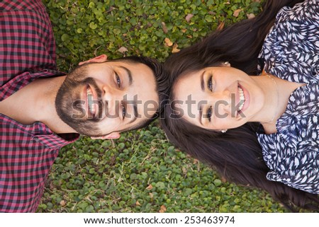 Top view of a good looking young couple relaxing at a park and smiling - stock photo