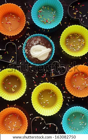 Top view of a group of colorful silicon cupcake forms on dark background - stock photo