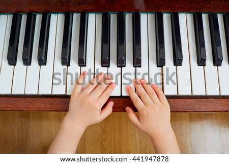 Top view of a hand, a child piano keyboard. Small child's hand on a piano keyboard. Education, child concept. - stock photo