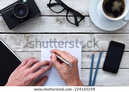 Top view of a hands with pen and coffee on workplace - stock photo