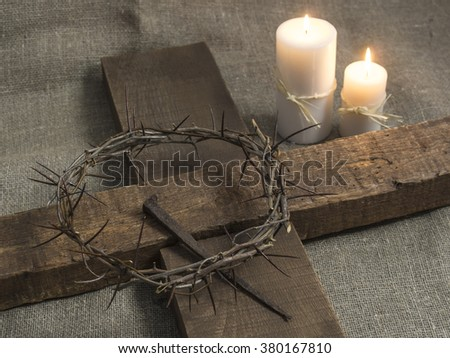 Top view of a holy cross, crown of thorns and candles on a burlap background. - stock photo