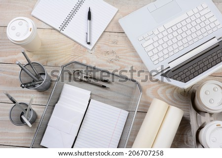 Top view of a home office desk with various items including: laptop computer, coffee cups, pad, notebook, pens, pencil cup, envelopes, in tray, compass, The primary color is shades of white. - stock photo