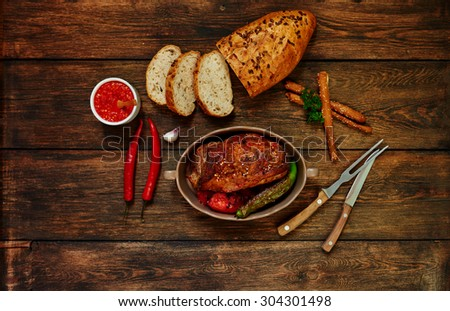 Top view of a housewife in the oven baked beef with vegetables, meat cooked in tomato sauce of garlic and spices, baked in bread with sunflower seeds - stock photo