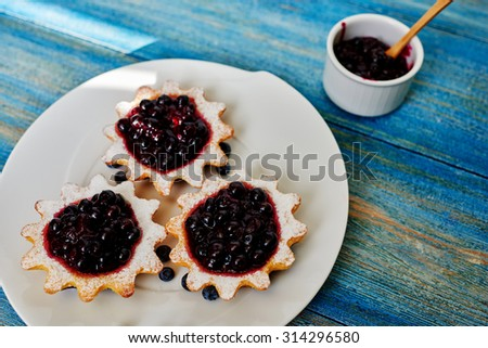 Top view of a housewife prepared it served dessert, small tarts made from unleavened dough of shortcrust pastry with homemade jam from berries, next to the plate there is a small bowl with jam - stock photo
