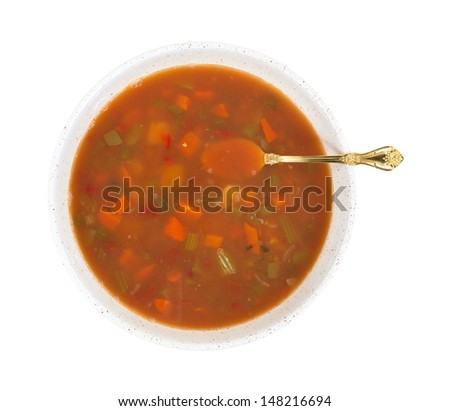 Top view of a large bowl of crab meat stew and vegetables with a gold spoon on a white background. - stock photo