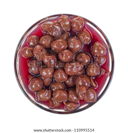 Top view of a large glass filled with tart pitted red cherries on a white background.