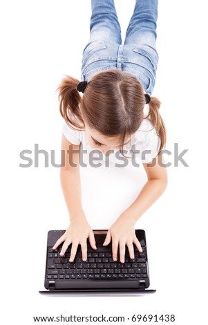Top view of a little girl lying on floor working with a laptop