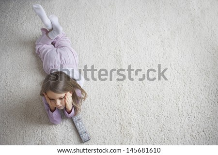 Top view of a little girl lying on rug with remote control - stock photo