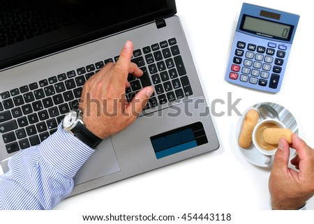Top view of a man who eats breakfast with coffee and cookies on the desk in a modern office - stock photo