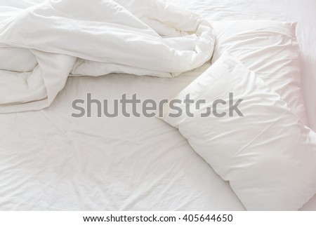 Top view of a messy bedroom with crumpled bedclothes. Bed room is not neatly arranged for new customers / guests to sleep in. - stock photo
