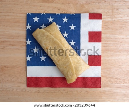 Top view of a microwaved chimichanga on an American flag motif napkin atop a wood table top. - stock photo