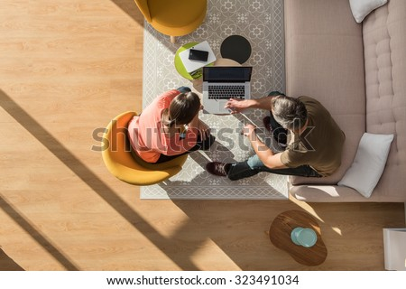 Top view of a middle age man and woman in casual clothes. They are sitting in a stylish vintage living room with wooden floor The grey hair man is showing some new project on the computer to the woman - stock photo