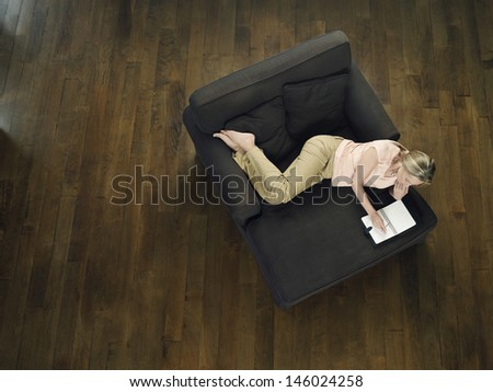 Top view of a middle aged woman sitting on sofa and using laptop - stock photo