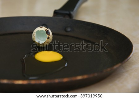 Top view of a/ one Raw Quail eggs to be fried on frying pan. whole and broken collection of egg. delicious bulls eye fried egg. decoration, food art,  topping on hot dog, hamburger - stock photo