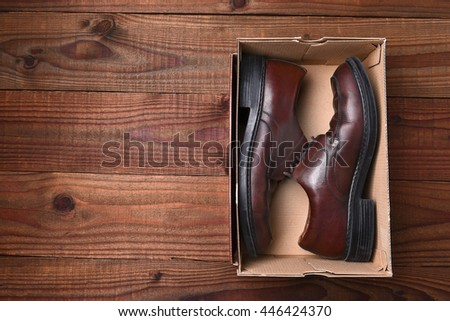 Top view of a pair of mens shoes in a box on a dark wood surface. Horizontal format with copy space.
