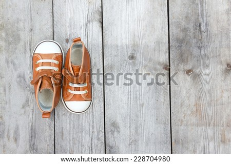 Top view of a pair of sneakers on wooden floor - stock photo