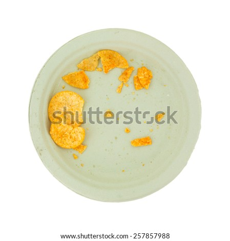 Top view of a paper plate with the remains of barbecue flavored potato chips on a white background. - stock photo