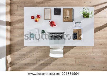 top view of a perfectly tidy white table with a laptop and a smartphone and other objects in the same color tone, sun casts graphics shadows  on the wooden floor - stock photo