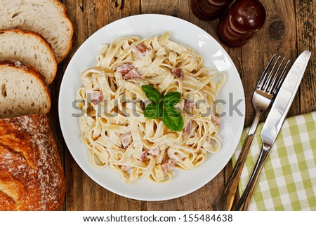 top view of a plate of tagliatelli carbanara italian cuisine in a traditional restaurant setting - stock photo