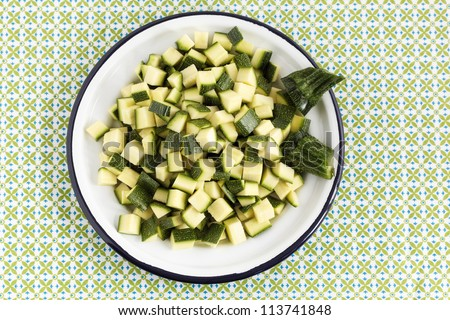 Top view of a plate with zucchini slices on a green pattern napkin.
