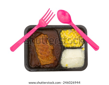 Top view of a prepared pork TV dinner with pink silverware on a white background. - stock photo